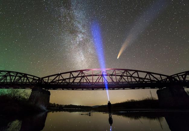 Homme avec lampe de poche debout sur la rive du fleuve sous un pont métallique illuminé sous un ciel étoilé sombre et une comète de neowise avec queue de lumière reflétée dans l'eau.