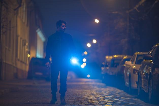 L'homme avec une lampe de poche inspecte la rue. le soir la nuit