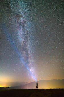 L'homme avec une lampe de poche principale se tient sur le fond du ciel étoilé. la nuit