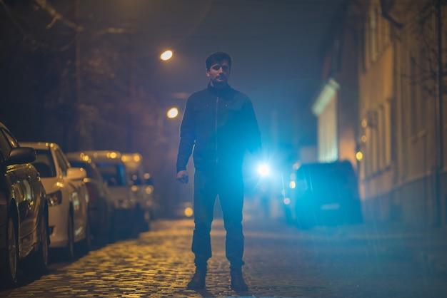 L'homme avec une lampe de poche se tient dans la rue. le soir la nuit
