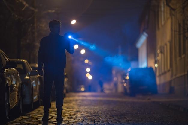 L'homme avec une lampe de poche se tient sur la route. le soir la nuit
