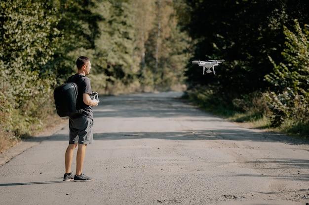 Homme lançant un drone en été
