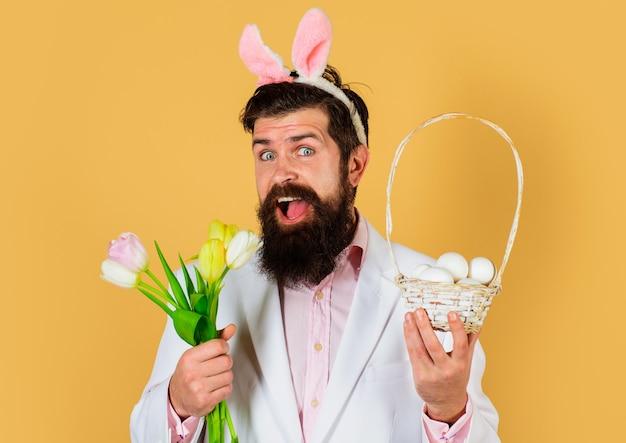 Homme lapin dans des oreilles de lapin avec des fleurs et des œufs de panier. concept de célébration de pâques. homme barbu en costume avec fleur de printemps.