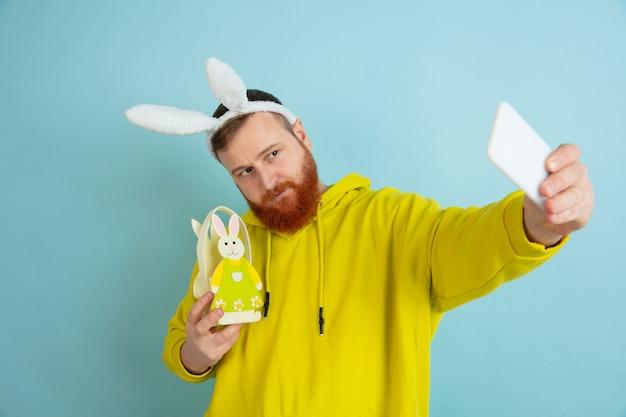Homme de lapin de pâques avec des émotions vives sur bleu