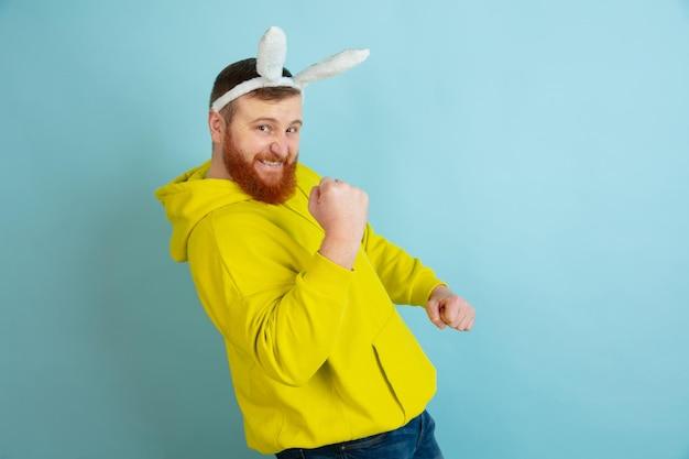 Homme de lapin de pâques avec des émotions vives sur fond bleu studio