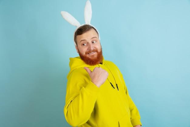 Homme de lapin de pâques avec des émotions vives sur le mur bleu