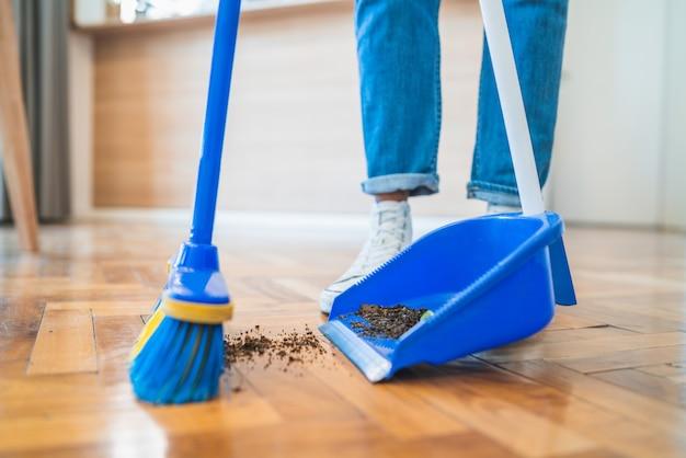 Homme latin balayant le plancher en bois avec balai à la maison.