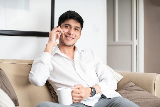 Homme latin en chemise blanche sur canapé tenant une tasse tout en parlant sur smartphone