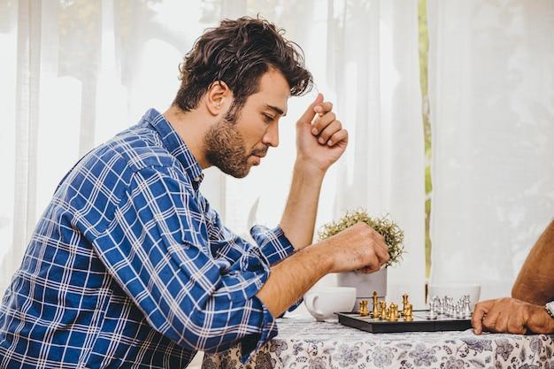 Homme latin jouant aux échecs à la maison pour une activité de vacances avec sa famille, il pense et a l'air sérieux