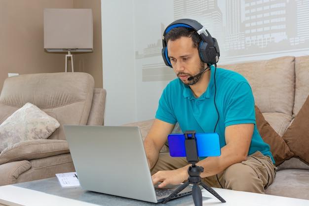 Homme latin prenant un cours en ligne depuis le canapé de sa maison (concept de cours en ligne et d'enseignement supérieur)