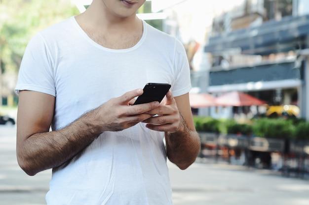 Homme latin tapant sur son téléphone.
