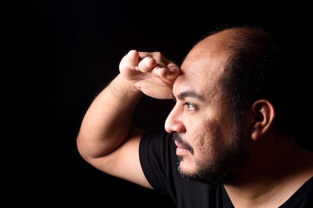 Homme latino-américain avec la main devant en regardant loin