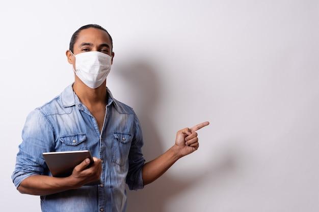 Homme latino avec masque facial tient une tablette et pointe vers l'espace vide sur fond blanc. distance sociale.