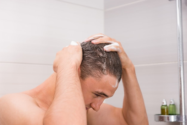 Homme lavant ses cheveux mouillés et en mousse dans la cabine de douche de la salle de bain