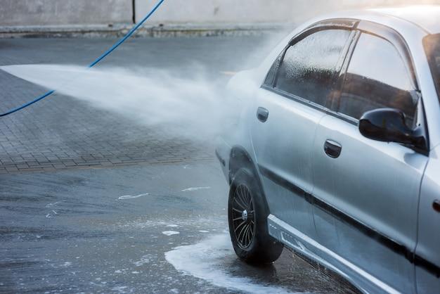 Un homme lave le détergent d'une voiture avec un jet d'eau dans un lave-auto en libre-service, gros plan