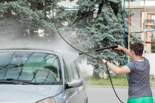 Un homme lave sa voiture dans un évier en libre-service en été à l'extérieur.