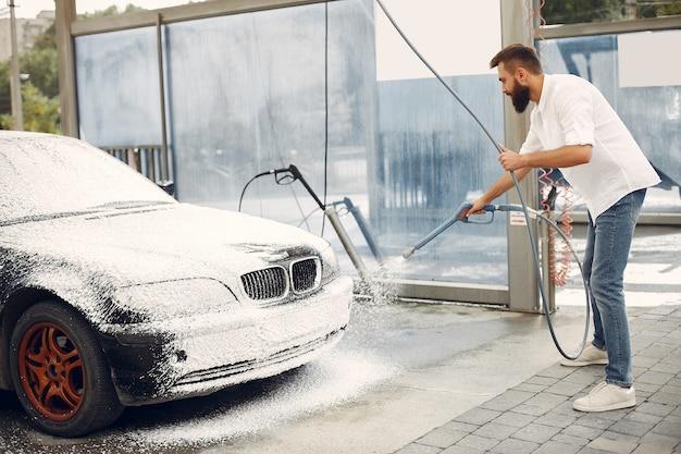 Homme lave sa voiture dans une station de lavage