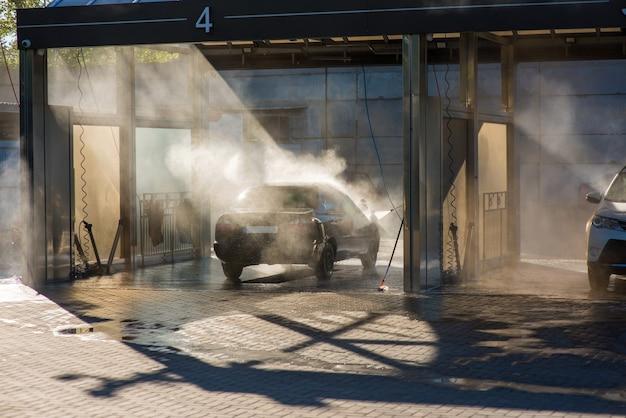 Un homme lave sa voiture avec un jet d'eau dans un lave-auto en libre-service dans les rayons arrière du soleil