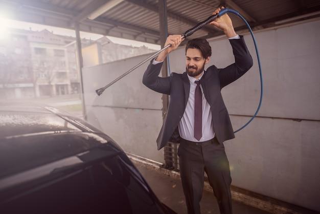 Homme lave sa voiture avec un lavage à haute pression.
