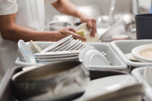 Homme lave-vaisselle sur évier au restaurant