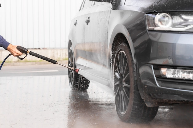 Un homme lave une voiture au lave-auto en libre-service. la laveuse de véhicules à haute pression vaporise de la mousse. mlada boleslav, 10.12.2019