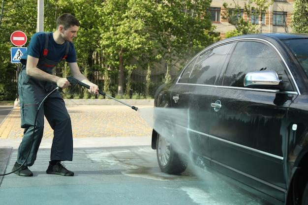 Un homme lave une voiture dans un lave-auto manuel.
