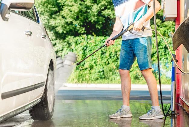 L'homme lave la voiture avec de l'eau à haute pression