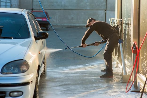 Un homme lave une voiture avec un jet d'eau dans un lave-auto en libre-service