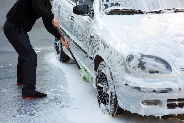 Un homme lave une voiture mousseuse avec une brosse dans un lave-auto en libre-service
