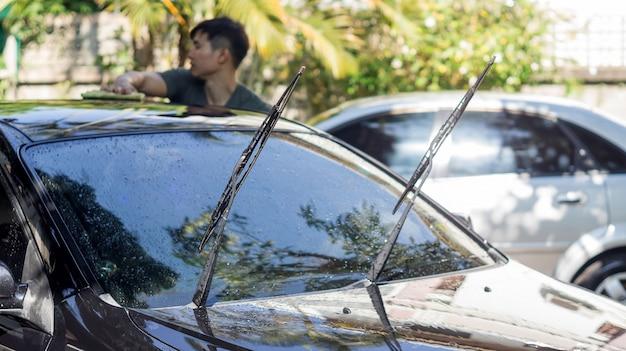 Homme lave la voiture noire.