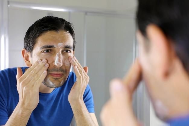 Homme laver le visage avec du savon de lavage