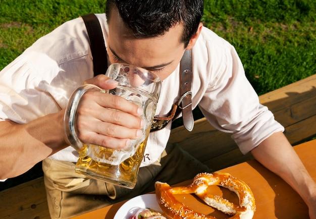 Homme à lederhosen buvant de la bière