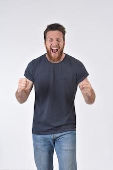 Homme levant les bras et souriant en signe de victoire sur backgroun blanc