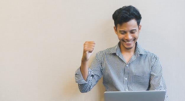 Homme levant la main avec le sentiment de réussite et heureux dans le défi en ligne