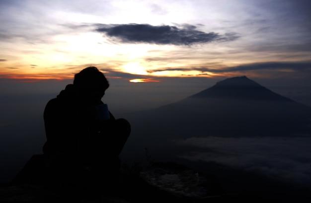 Homme et le lever du soleil en montagne
