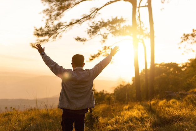 Homme lever la main dans les airs pendant le coucher du soleil au sommet de la montagne
