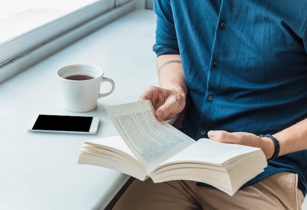 Homme lisant avec un café
