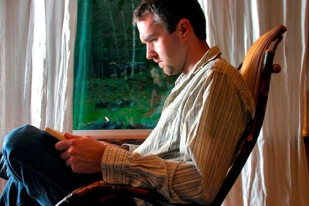 Homme lisant dans la chaise berçante