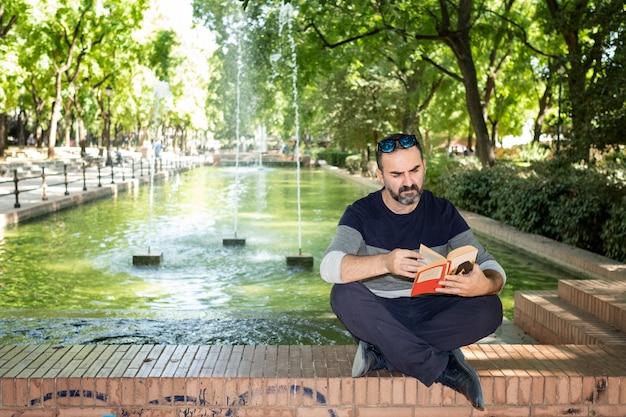 Homme lisant un livre dans un parc