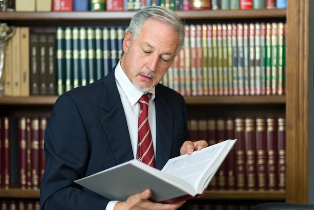 Homme lisant un livre dans sa bibliothèque