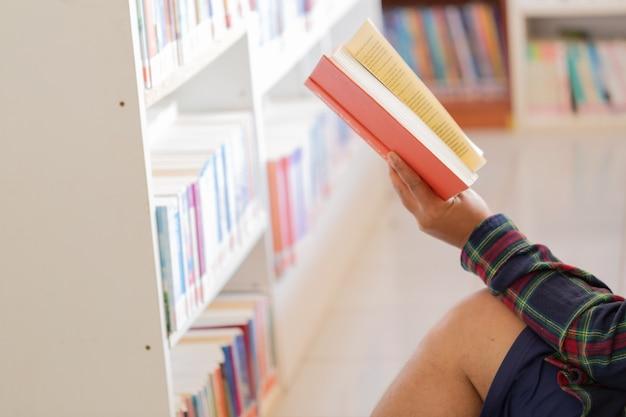 Homme lisant livre dans ses mains dans la bibliothèque.