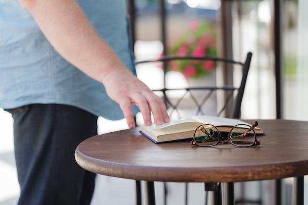 Homme lisant un livre avec du café ou du thé