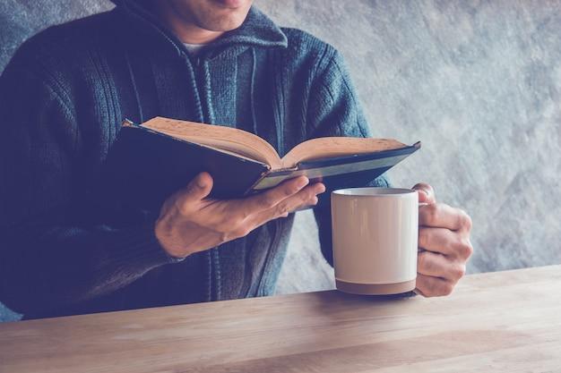 Un homme lisant un livre avec du café ou du thé