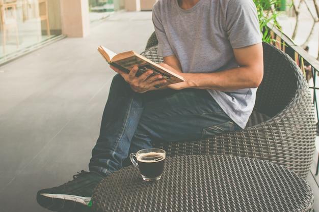 Un homme lisant un livre avec du café