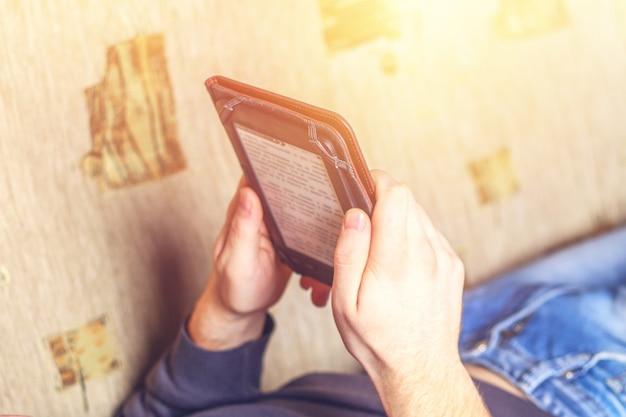 Homme lisant un livre électronique sur une tablette numérique.