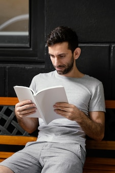 Homme lisant un livre intéressant sur un banc