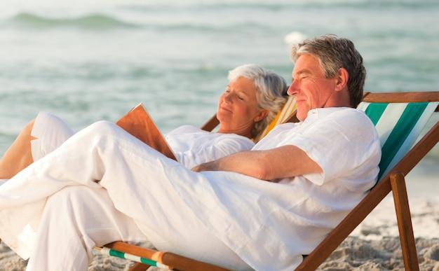 Homme lisant un livre pendant que sa femme dort