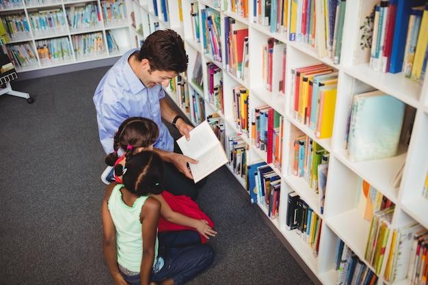 Homme lisant un livre pour deux enfants