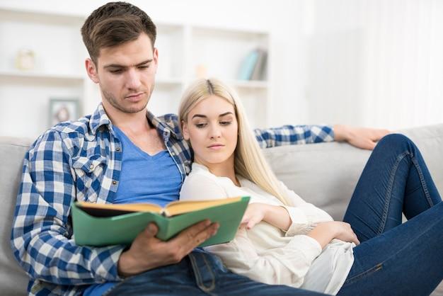 L'homme lisant le livre près de la femme sur le sofal