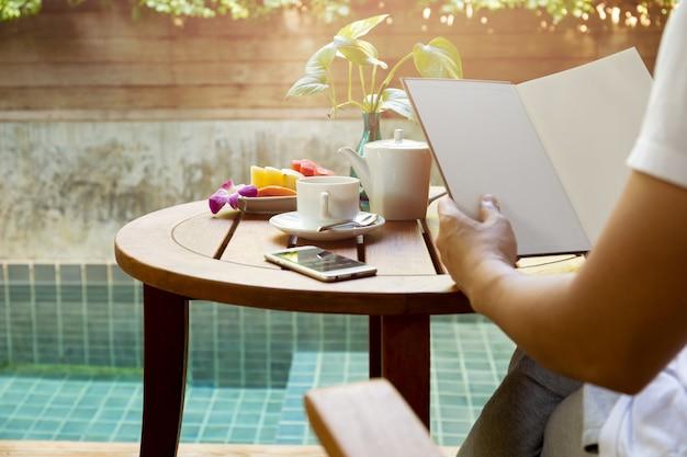 Homme lisant un livre avec une tasse de café et de fruits frais sur une table en bois.